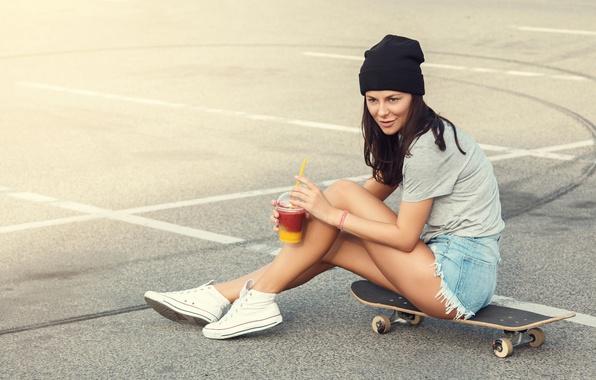 Картинка асфальт, девушка, стакан, шапка, шорты, фигура, брюнетка, футболка, коктейль, ножки, скейт, кроссовки, скейтборд