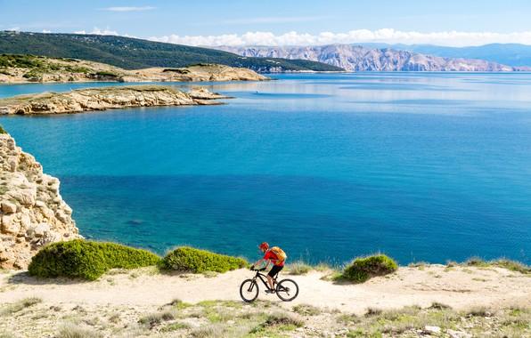 Картинка солнце, пейзаж, горы, велосипед, отдых, берег, спорт, шорты, остров, футболка, залив, перчатки, шлем, велосипедист, рюкзак, …