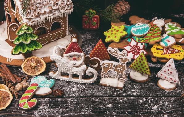 Картинка ветки, праздник, доски, рождество, печенье, сахар, ёлка, шишки, фигурки, выпечка, пряности, пряники, пудра, пряничный домик