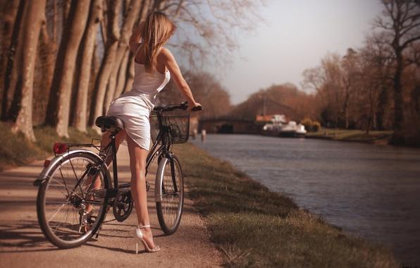 Картинка девушка, солнце, деревья, природа, велосипед, поза, парк, фигура, платье, прическа, туфли, ножки, речка, в белом, …