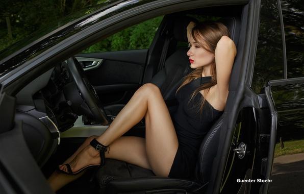 Картинка авто, девушка, поза, кресло, макияж, фигура, платье, прическа, туфли, шатенка, ножки, сидит, салон, в черном, ...
