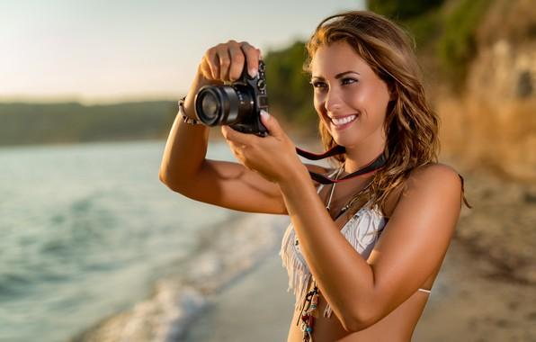 Картинка море, пляж, купальник, солнце, поза, улыбка, макияж, прическа, фотоаппарат, шатенка, стоит, фотографирует, симпатичная, боке, на …