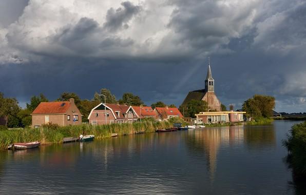 Картинка небо, солнце, облака, деревья, тучи, река, камыши, дома, лодки, церковь, Нидерланды, Oudendijk