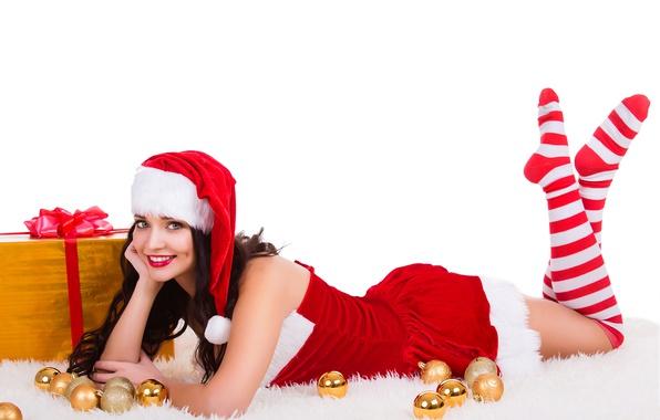 Картинка шарики, подарок, шапка, игрушки, новый год, рождество, чулки, макияж, платье, брюнетка, прическа, белый фон, лежит, …