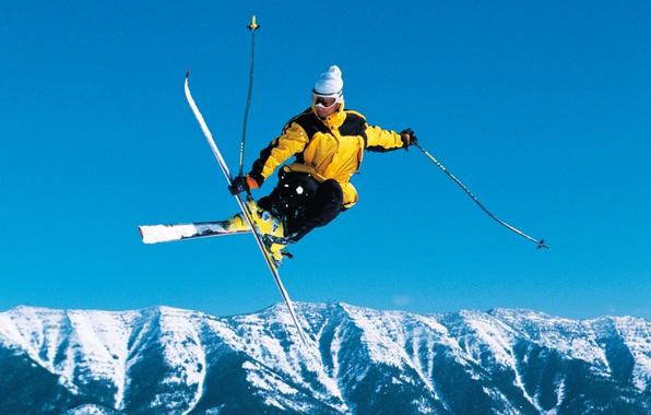 Картинка зима, лес, небо, снег, пейзаж, горы, прыжок, шапка, лыжи, палки, очки, куртка, спортсмен, солнечно, фристайл, …