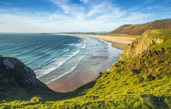 Картинка море, зелень, пляж, небо, трава, солнце, облака, горы, скалы, побережье, Англия, Wales