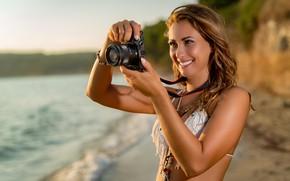 Обои на берегу, солнце, море, макияж, стоит, купальник, боке, прическа, пляж, улыбка, шатенка, фотографирует, симпатичная, фотоаппарат, ...