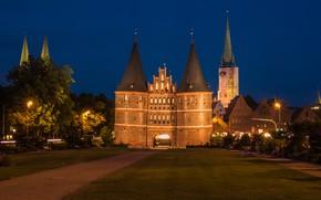 Картинка деревья, ночь, огни, газон, дома, Германия, фонари, дорожка, памятник, башни, архитектура, Holstentor, Luebeck, Голштинские ворота
