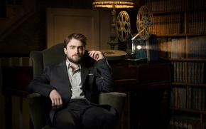 Картинка поза, книги, костюм, актер, полумрак, сидит, Дэниэл Рэдклифф, фотосессия, в кресле, полки, Daniel Radcliffe, луч …