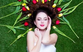 Картинка зелень, девушка, цветы, улыбка, газон, желтые, макияж, брюнетка, прическа, тюльпаны, красные, лежит, 8 марта, симпатичная, …