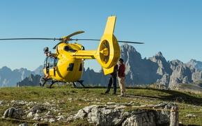 Обои камни, желтый, скалы, небо, солнце, возвышенность, люди, вертолет, трава, горы, пейзаж