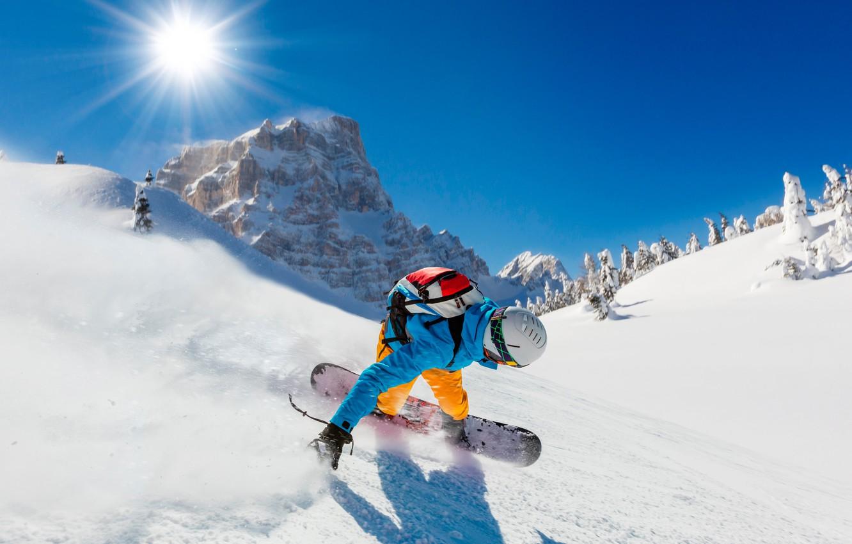 Фото обои зима, небо, солнце, лучи, снег, деревья, горы, скалы, сноуборд, спорт, скорость, склон, костюм, перчатки, шлем, …