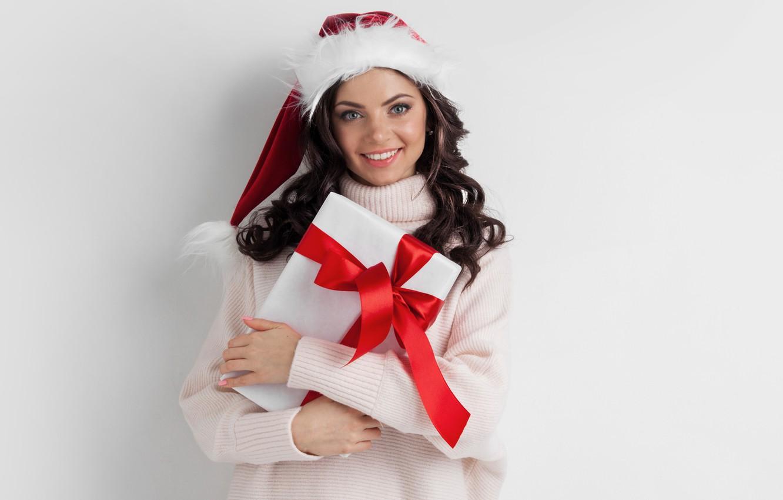 Фото обои фон, праздник, коробка, подарок, шапка, новый год, макияж, брюнетка, прическа, снегурочка, стоит, красная, держит, ленточки, …