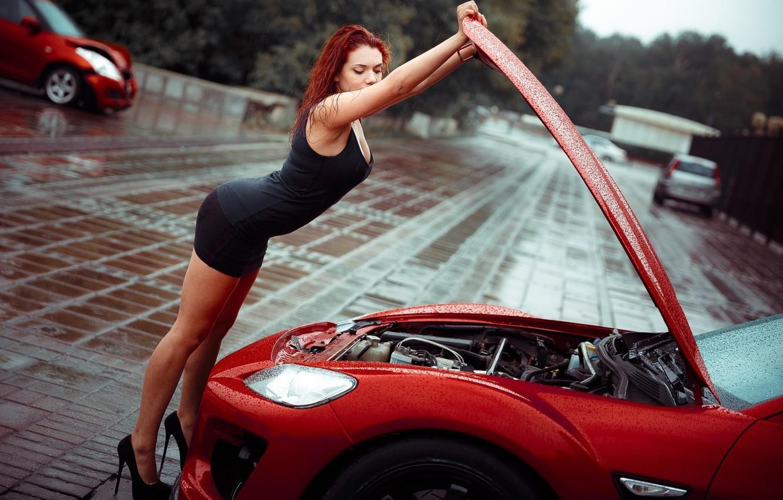Фото обои девушка, капли, красный, поза, дождь, капот, фигура, платье, туфли, рыжая, ножки, автомобиль, мотор, в черном, …