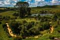 Картинка солнце, поля, домики, Hobbiton, холмы, деревья, люди, Новая Зеландия, озеро, зелень, лето, облака, трава, дорожка, ...