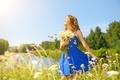 Картинка цветы, улыбается, держит, рыженькая, прическа, речка, девушка, лужайка, солнце, платье, букет, природа, деревья, боке, закрыла, ...